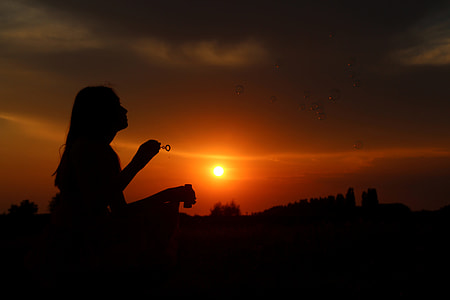 silhouette photo of a woman holding bubble making stick