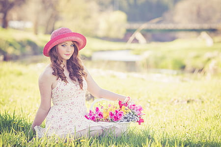 photo of a woman sitting on ground holding bouquet of basket flower