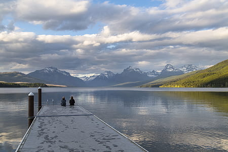 two person sitting on black wooden dock while looking at mountain with body of water scenery during daytime