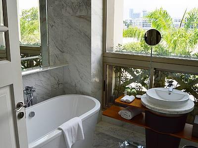 bath tub near glass window and vanity sink