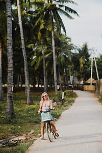 woman riding a bicycle beside green coconut trees