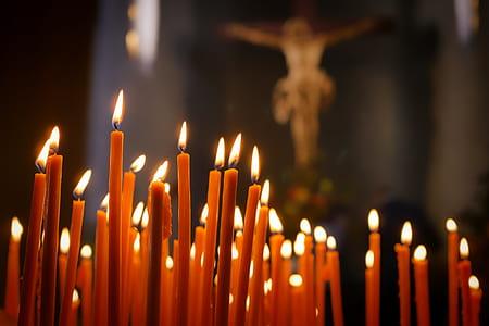lighted candle near crucifix photo