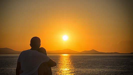 couple hugging near calm sea during golden hour