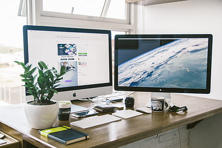 iMac and flat screen monitor on brown wooden desk
