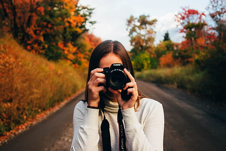 photo of woman holding camera