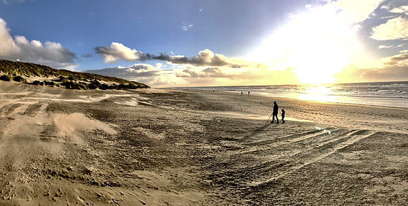 Photo of People Walking on Brown Sand