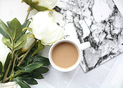 white peony flowers beside cup of coffee