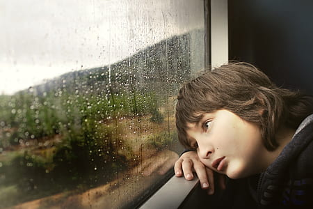 boy resting cheek on hand while looking outside window