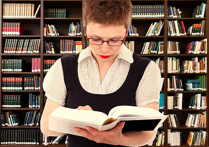 woman reading a book with books in the background