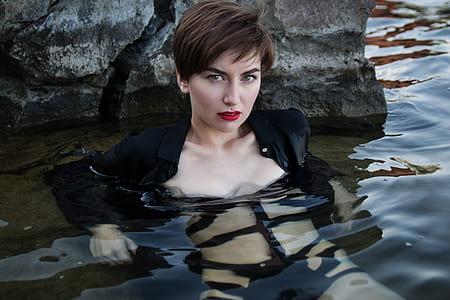 woman wearing black jacket in body of water during daytime