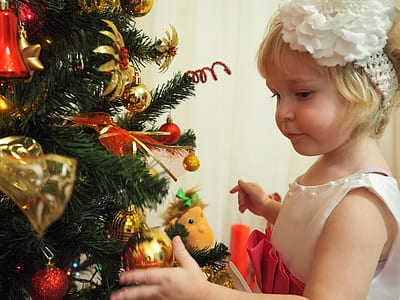 girl holding bauble of Christmas tree