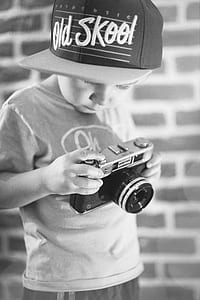 grayscale photo of boy holding rangefinder camera