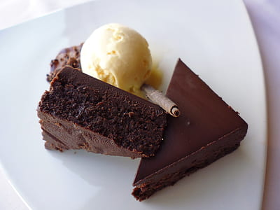 two sliced brownies beside scoop of ice cream on white ceramic plate