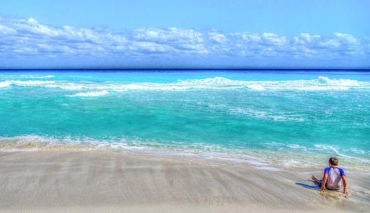 man wearing white and blue raglan shirt sitting in seashore facing the blue sea during daytime