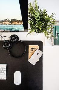 space gray iPhone 6 beside black full-size headphones
