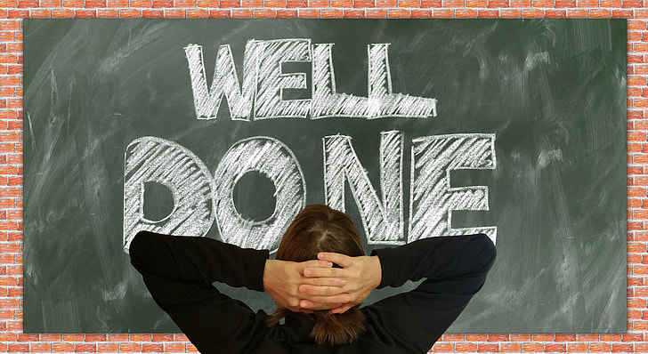 woman looking at the Well Done board