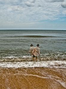 man in beige dress shirt walking beside sea