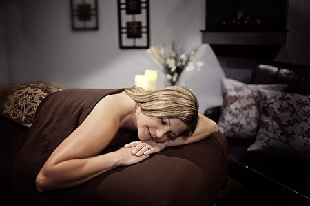 woman lying on brown couch