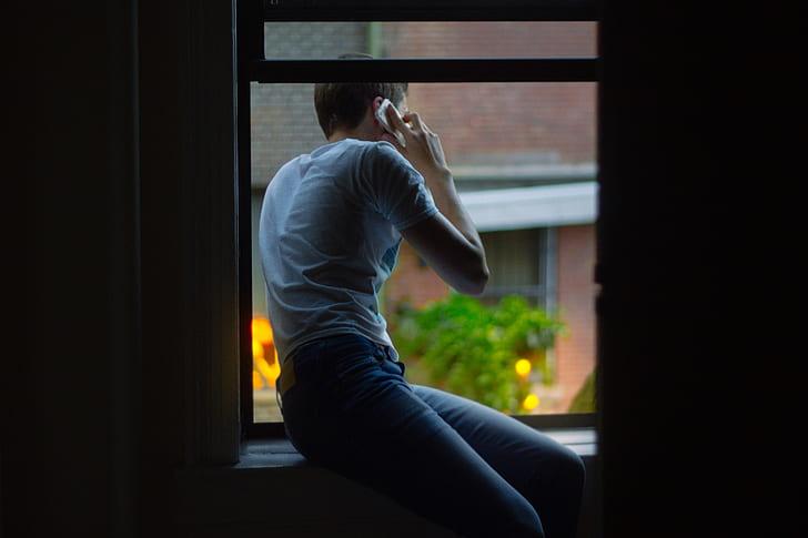 Royalty-Free photo: Man sitting on window using smartphone | PickPik