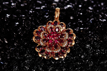 gold-colored red gemstone encrusted pendant