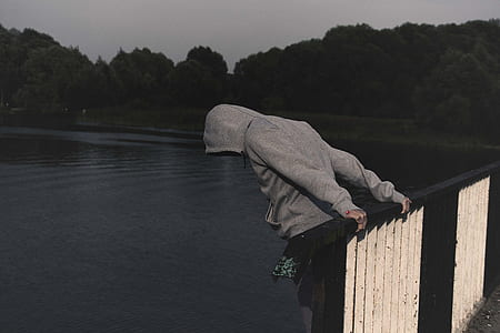 person wearing grey pullover hoodie holding on brown and white metal railings overlooking body of water