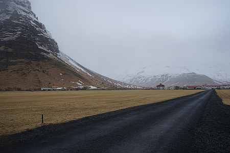 black asphalt road near rocky mountain