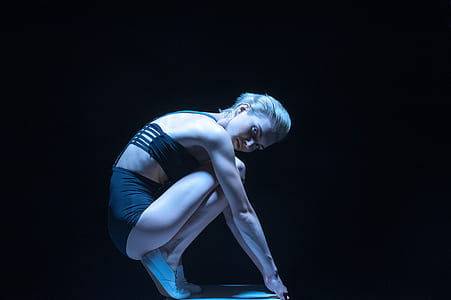 woman wearing black underwear crouching on tiptoes with black background