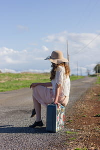 woman sitting on suit case beside road