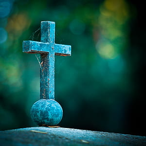 selective focus photo of a cross on grey pavement