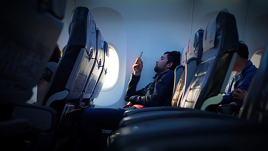man wearing black dress shirt holding phone in the airplane seat