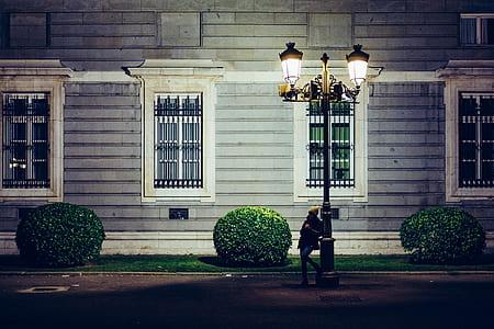 woman leaning on black steel post lamp near house