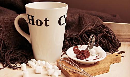 white and black ceramic mug near brown textile