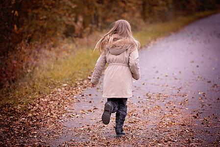 girl wearing beige hoodie running on road during daytime