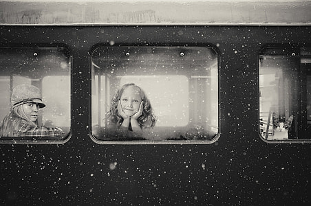 grascale photo of girl inside train