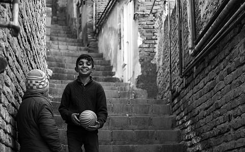 grayscale photography of boy holding ball on stairs