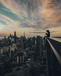 person sitting on the top of building photography during daytime