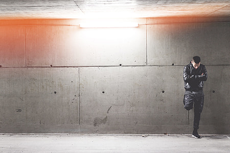 Young Man Standing In Front of Concrete Wall