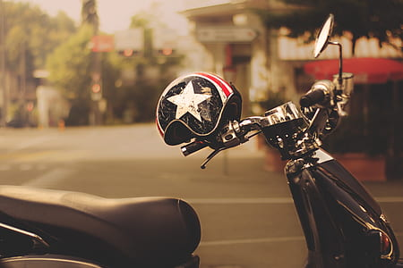 black motor scooter with black helmet