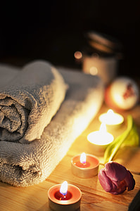 massage table with towel beside candle tealight