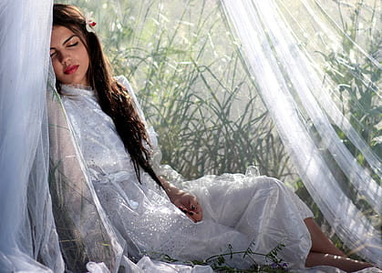 woman in white laying on white textile