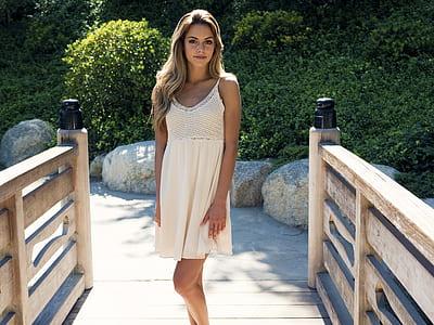 woman in white scoop-neck spaghetti-strap dress standing on beige wooden bridge during daytime