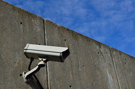 gray bullet-style security camera on wall