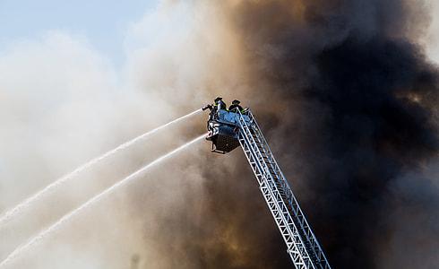 two fireman on manlift truck under black smoke during daytime