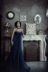 women's blue spaghetti strap dress stand near white fireplace surround