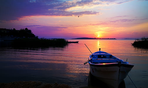photo of white row boat on body of water during sunset
