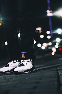 person wearing white-and-black Air Jordan 8 shoes