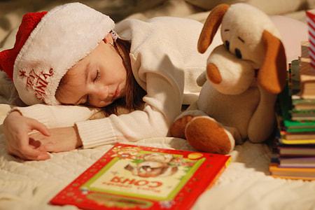 girl wearing white and red santa hat sleeping
