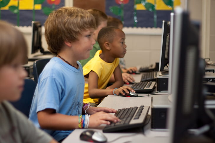 group of boys playing on computers
