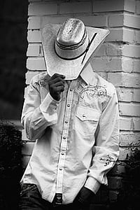 grayscale photography of man wearing floral dress shirt and cowboy hat leaning on bricked wall