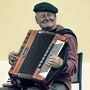 man wearing flat hat and playing accordion